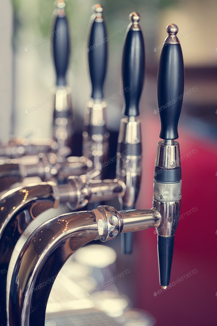 Silver and black beer taps close up in a pub