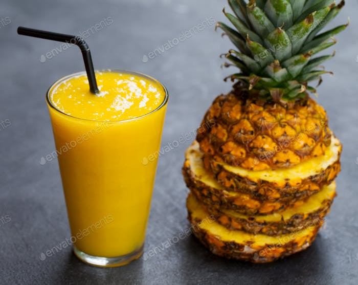 Pineapple with Tropical Fruit Juice, Smoothie on Dark Stone Background. Close up.