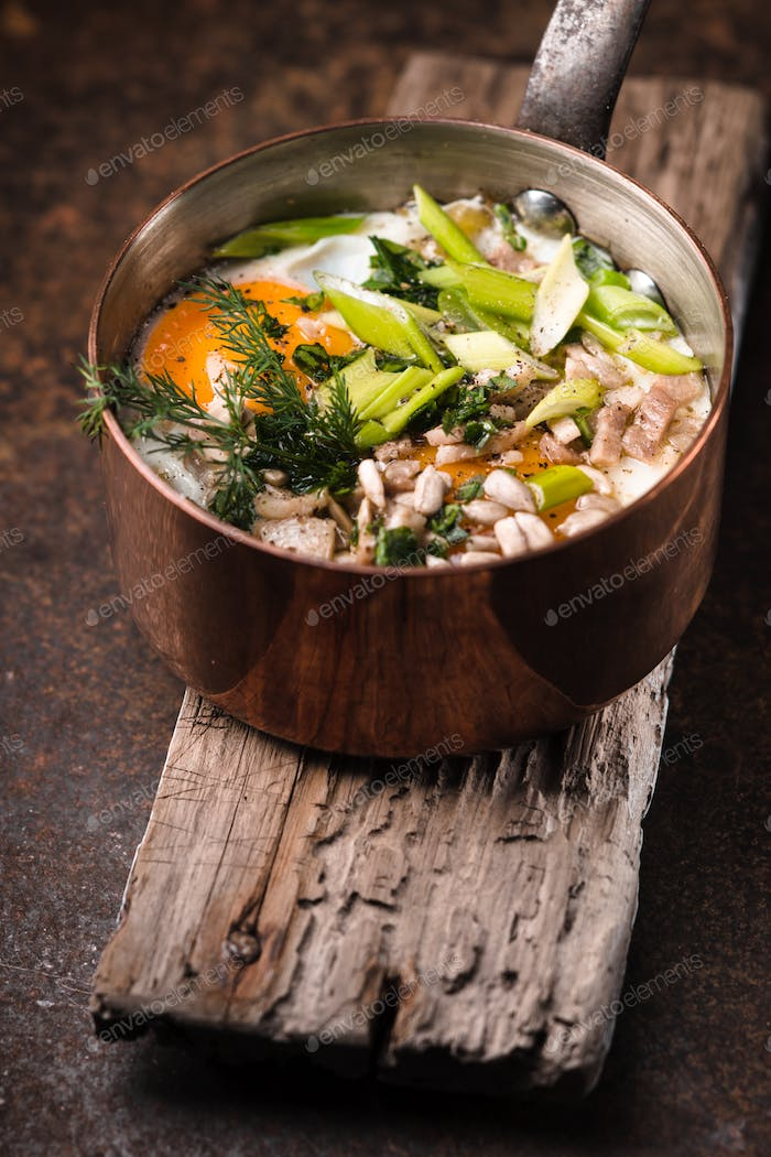 Fried eggs  with greens in the copper pot on the metal table