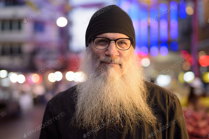 Face of mature bearded tourist man with eyeglasses in Chinatown at night
