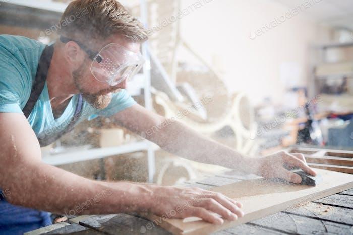 Ремесленник с помощью наждачной бумаги