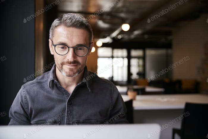 Middle aged white male creative sitting in an office looking at laptop computer screen, close up