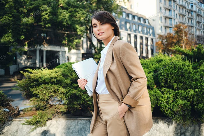 Young businesswoman in beige suit standing with laptop intently looking in camera on city street