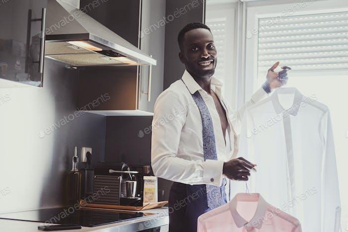 Cheerful african man is choosing shirt