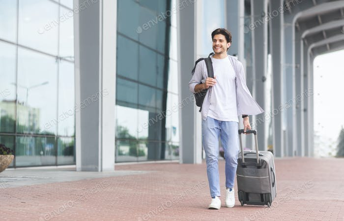 Happy man walking with luggage near modern airport building