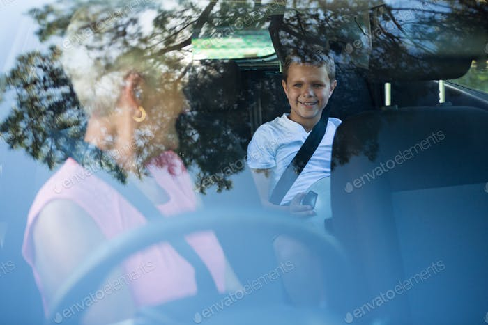Grandmother driving a car while grandson sitting in the back seat
