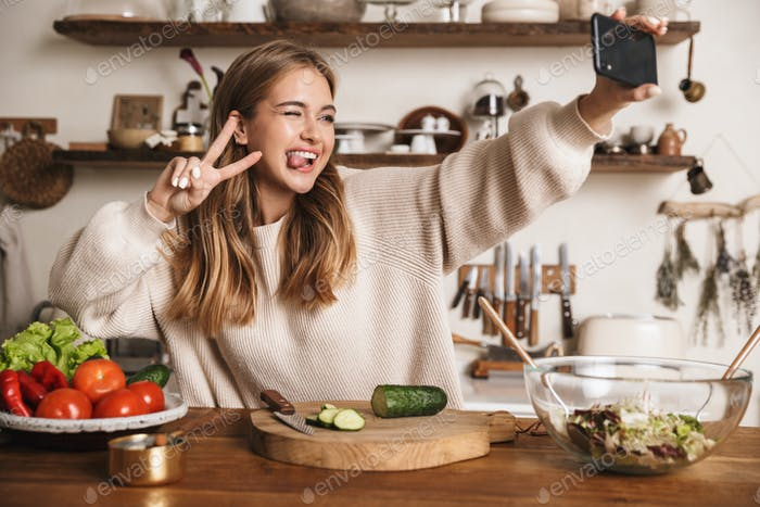 Image of funny cute woman taking selfie on cellphone and gesturing peace sign