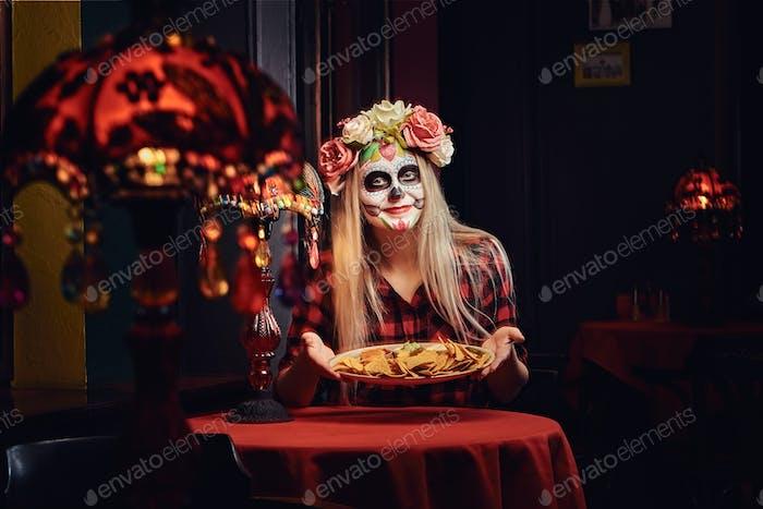 Junge blonde Mädchen mit Untoten Make-up in Blumenkranz essen Nachos in einem mexikanischen Restaurant.