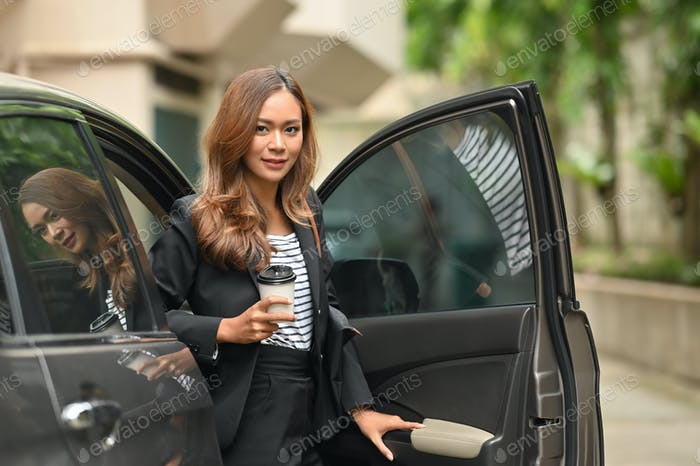 Attractive businesswoman stand on car door with looking at camera.