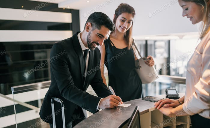 Two business people check-in at hotel reception.