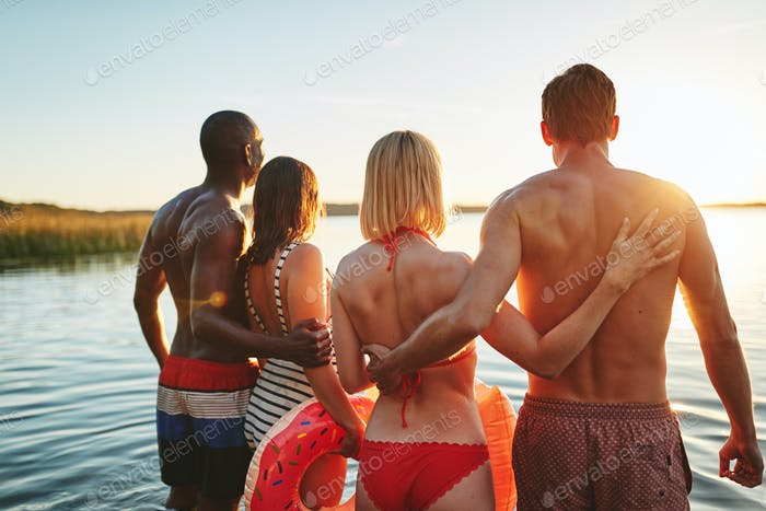 Two young couples standing in a lake watching the sunset
