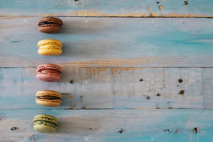 Background blue wooden table with five macarones with chocolate and cream