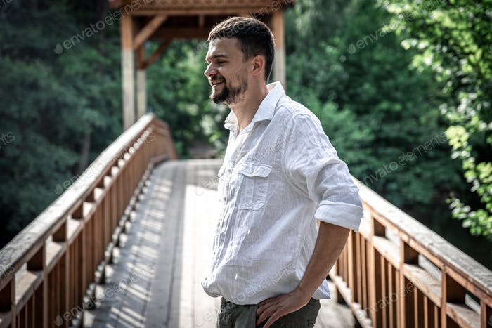 Portrait of a young man on a bridge in the forest.