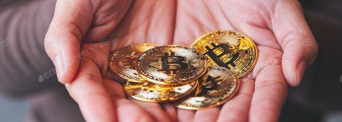 Imagen de cerca de una mujer sosteniendo y mostrando bitcoins de color dorado en las manos