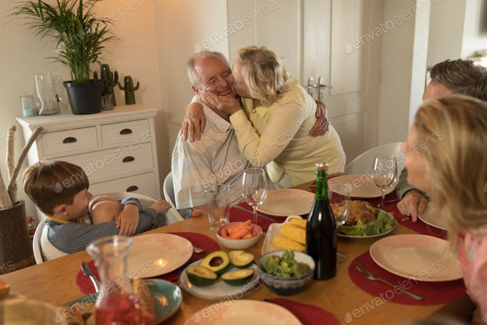 Multi-generation family interacting with each other while having meal on dining table at home