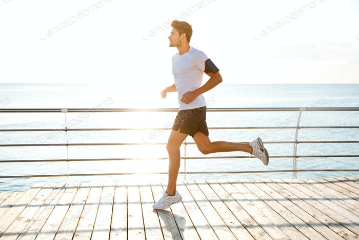 Handsome man athlete running outdoors in the morning