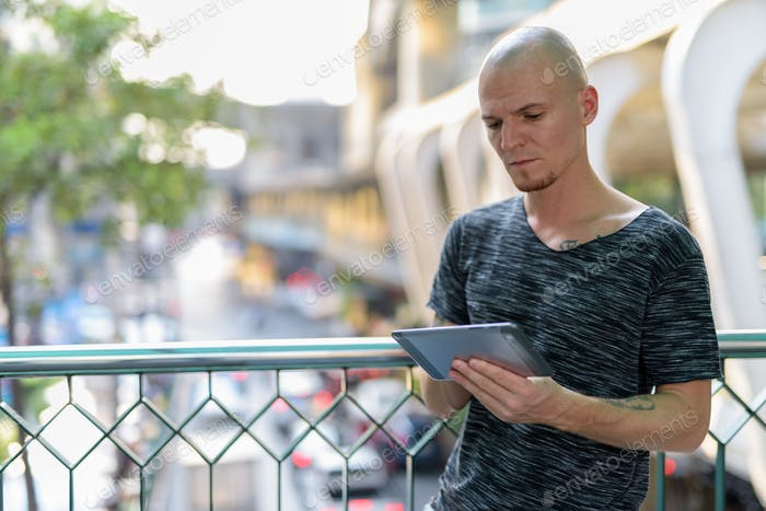 Young handsome bald man using digital tablet on the foot bridge