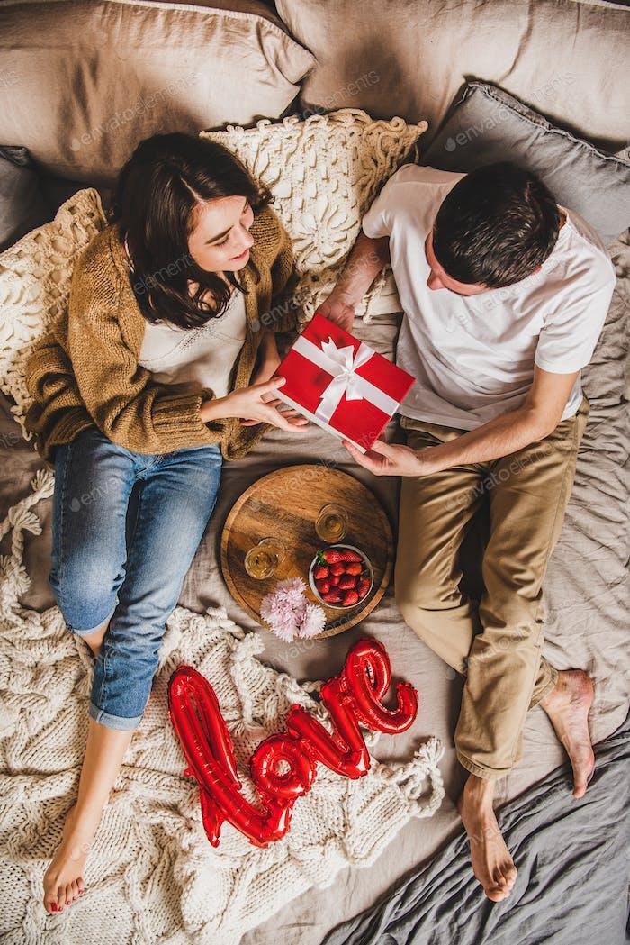 Junge glückliche paar sitzen im Bett und geben Geschenke