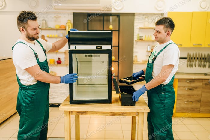 Two workers in uniform repair refrigerator at home