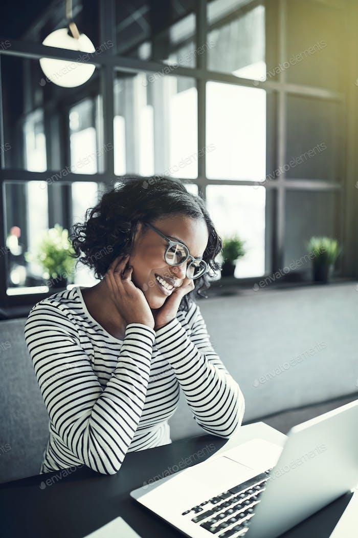 Молодая африканская женщина улыбается и в чате онлайн
