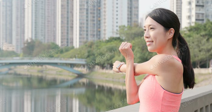 Sport woman stretching arm at park