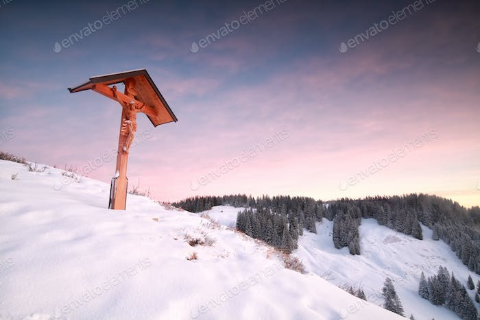 cross on top on mountain in winter