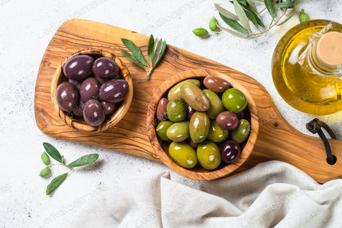Olives in wooden bowls and olive oil bottle on white background