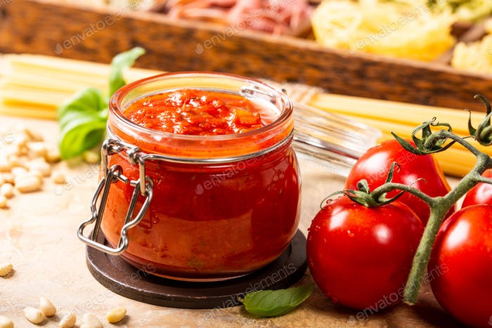 Glass jar with homemade classic spicy tomato pasta or pizza sauce.