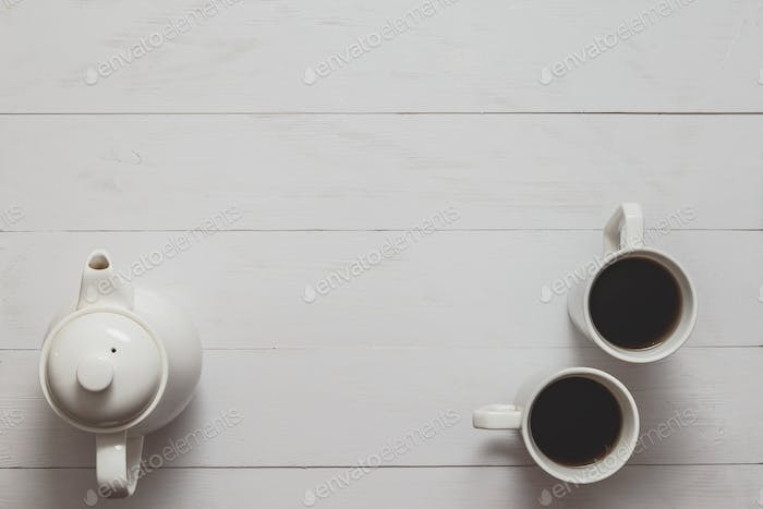 Tea still life with kettle and two cups on white wooden desk.
