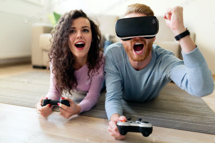 Glückliches junges Paar Video spiele mit Virtual Reality Headsets