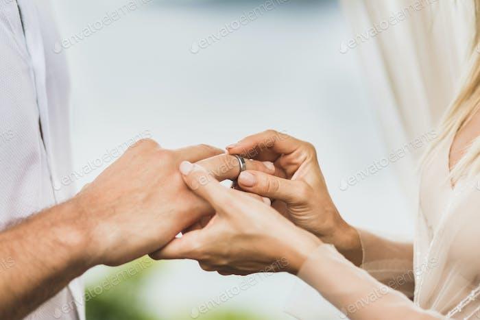Novia poniendo anillo de bodas en la mano del novio de cerca. Símbolo de amor y compromiso.