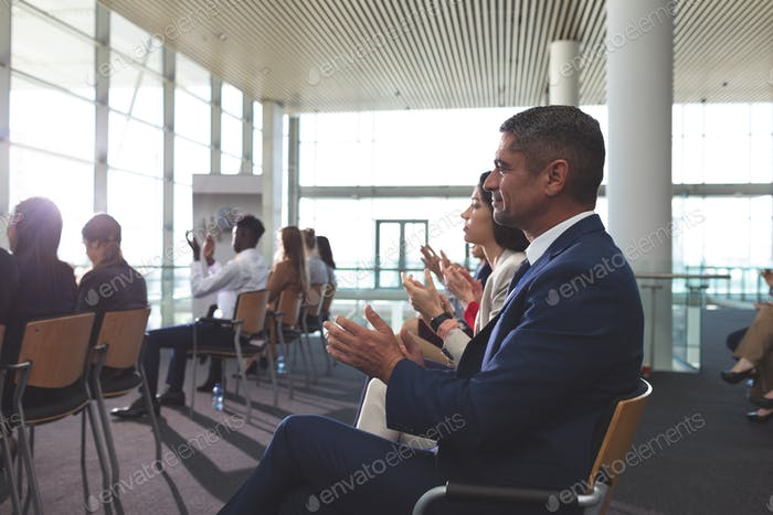 Side view of diverse business people applauding at a business seminar in office building