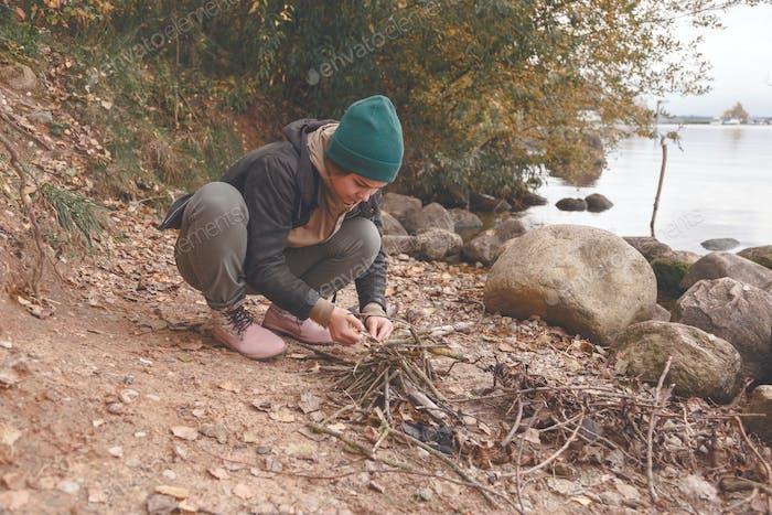 Junge Frau macht Kamin am Strand