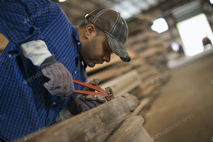 A man working in a reclaimed timber yard, using a tool to remove metal from a piece of timber.