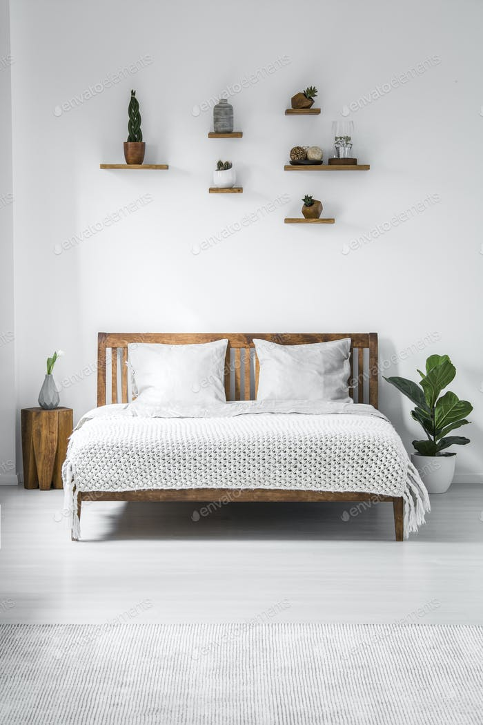 Wooden framed double bed with two pillows and a blanket, and sma