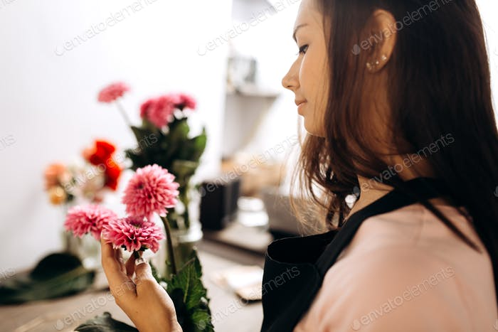 Young woman florist touches with her hand fresh pink chrysanthemums