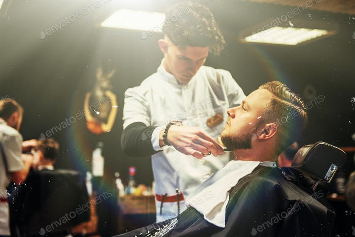 The Barber man in the process of cutting the beard of client electric clippers in the barbershop.