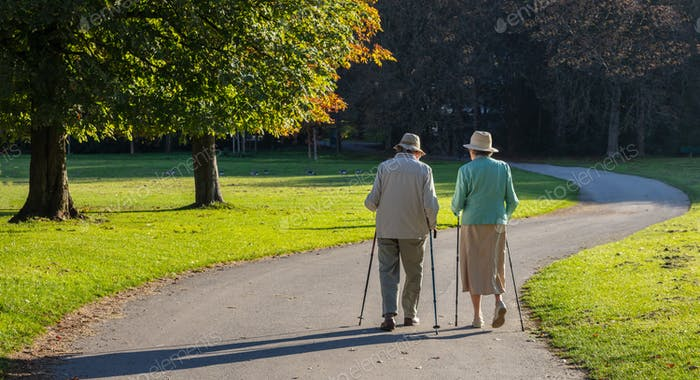 City park, Munich, Germany. View of a mature couple walking on a path