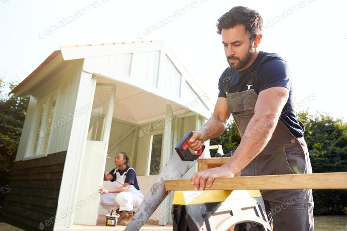 Male Carpenter With Female Apprentice Sawing Wood To Build Outdoor Summerhouse In Garden