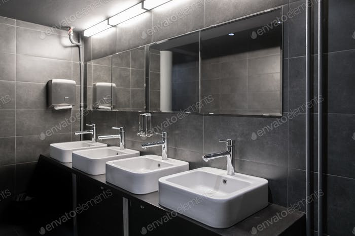 Faucets with washbasin in public restroom in grey colors