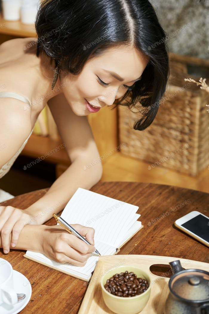 Beautiful woman writing down plans