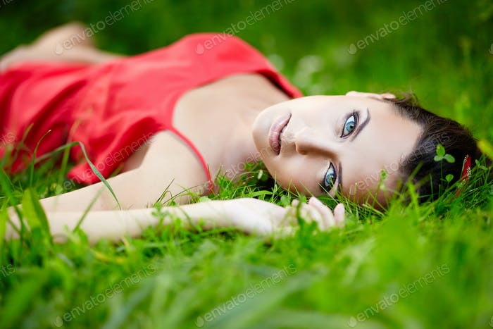Model lying in green summer bright grass in the park