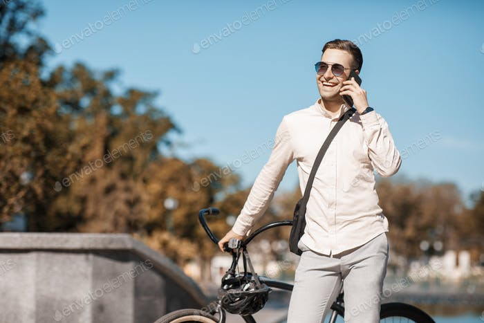 Handsome hipster at park. Businessman with bicycle speaks on phone