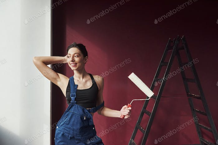 Positive emotions. Young housewife decided to glue wallpaper in her new house in the room