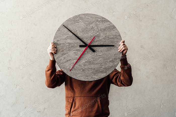 Unrecognizable person covering face with stylish round wooden clock