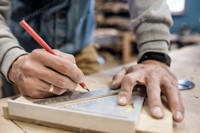 Verwenden einer Geraden, um eine Linie auf einem Brett zu zeichnen.