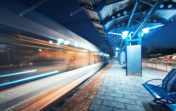 Blurred high speed train on the railway station at night