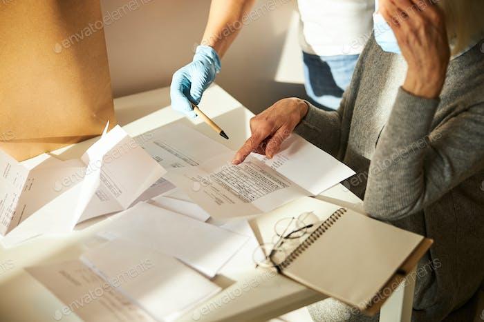 Seniorin und ihr Hausmeister prüfen Stromrechnungen