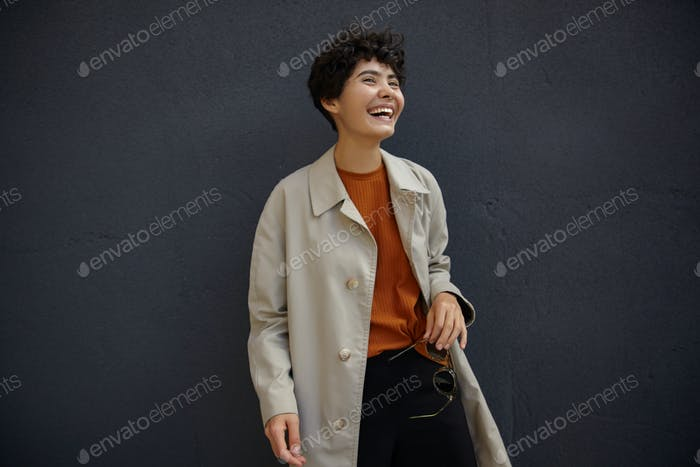 Joyful young attractive female with casual hairstyle wearing stylish clothes
