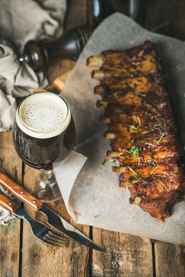 Roasted pork ribs with garlic, rosemary and glass of beer